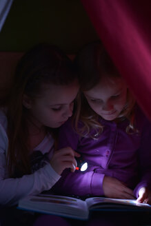 Two girls reading a book with a torch in their selfmade cave - NYF000003