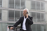 Businessman with bicycle telephoning with smartphone - SGF001708