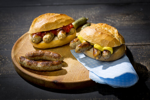 Nuremberg grilled sausage, wheat roll with mustard ketchup and gherkin on wooden plate - MAEF010767