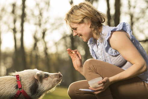 Woman taming piglet in park - TAM000189