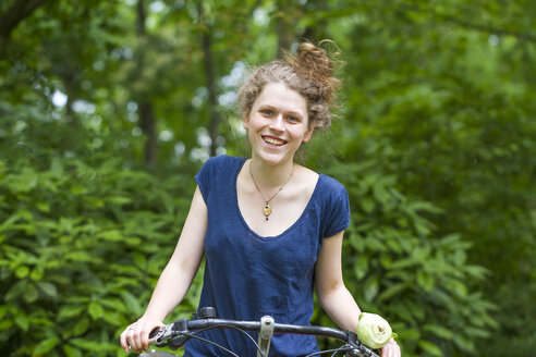 Portrait of smiling young woman riding bicycle - SGF001713