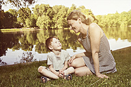 Mother and son sitting on a meadow in a park - TAM000117