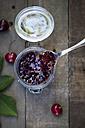 Jar of cherry jam and cherries on wood - LVF003542