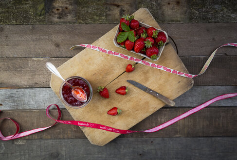Glass of homemade strawberry jam, ribbon and box of strawberries - LVF003551