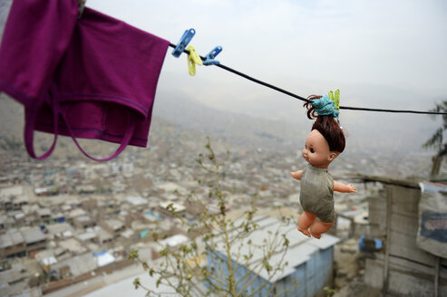 Peru, Lima, Huaycan, doll hanging on washing line - FLKF000616