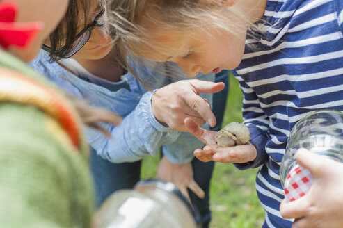 Germany, Children looking at snails - MJF001529