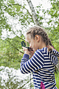 Germany, Girl looking through compass - MJF001547