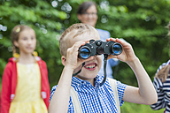 Germany, Boy with binoculars watching animals - MJF001551