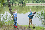 Germany, Boys at pond throwing stones - MJF001573