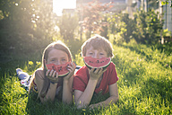 Boy and girl lying on a meadow covering part of her face with slice of watermelon - SARF001994