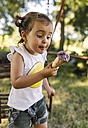 Little girl trying to eat ice cream - MGOF000305