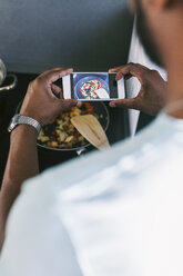 Young man photographing his prepared food with smartphone in the kitchen - EBSF000707