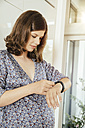 Pregnant woman looking at her smart watch - MFF001769
