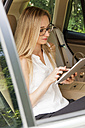 Blond woman sitting on back seat of a car using digital tablet - JUNF000368