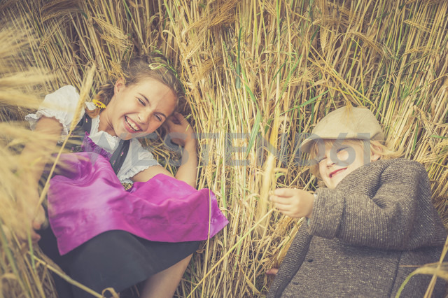 Germany, Saxony, two children lying in a grain field having fun - MJF001581 - Jana Mänz/Westend61