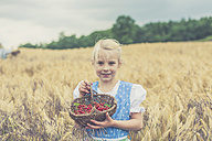 Germany, Saxony, portrait of smiling girl standing in a grain field with basket of red currants - MJF001589