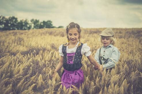 Germany, Saxony, boy and girl walking in a grain field - MJF001594