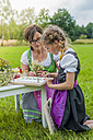 Germany, Saxony, girl wearing dirndl learning to draw plants - MJF001609