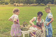 Germany, Saxony, three little girls and their educator in traditonal clothes on a meadow - MJF001615