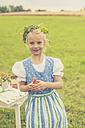 Germany, Saxony, portrait of smiling girl with floral wreath and dirndl holding carrot in her hand - MJF001621
