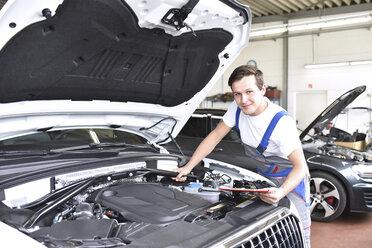 Mechanic examining engine of a car in a garage - LYF000444