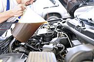 Car mechanic refilling engine oil - LYF000438