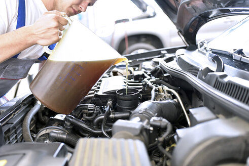 Car mechanic refilling engine oil - LYF000438