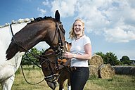Germany, Wiesenau, laughing blond woman with two horses on a meadow - TAM000246