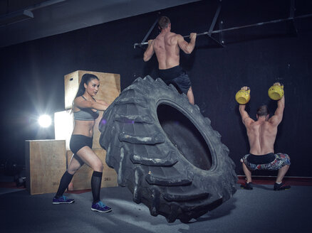 Three CrossFit athletes at workout - MADF000321