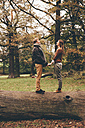 Young couple in love holding hands on a tree trunk in an autumnal park - CHAF000202