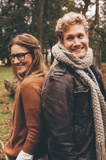 Happy young couple standing back to back in an autumnal park - CHAF000205