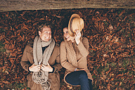 Young couple lying side by side on autumn leaves in an park - CHAF000216