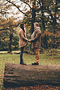 Young couple in love holding hands on a tree trunk in an autumnal park - CHAF000217