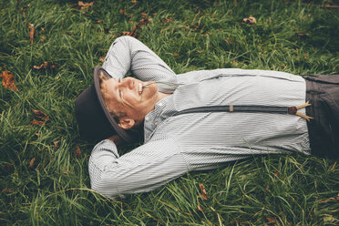 Smiling young man lying on a meadow with hands behind his head - CHAF000229
