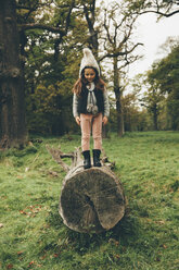 Little girl wearing cap standing on a tree trunk in autumnal park - CHAF000238