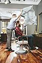 Barber tying cape around customer - MADF000338