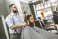 Barber tying cape around customer - MADF000344