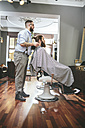 Barber cutting beard of a customer and looking in mirror - MADF000342