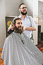 Barber cutting beard of a customer and looking in mirror - MADF000357