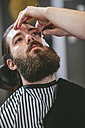 Man with full beard getting a shave at the barber - MADF000349