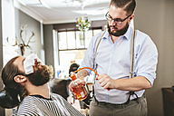 Barber spraying aftershave on beard of a customer - MADF000358