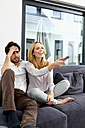 Couple sitting together on couch watching TV show - CHAF000282