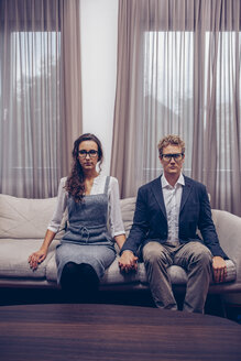 Young couple at home sitting on sofa with blank expression - CHAF000303