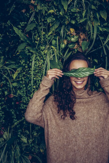 Smiling young woman covering her eyes with a leaf - CHAF000330
