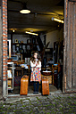 Girl standing at garage with two suitcases - CHAF000333
