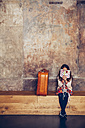 Girl sitting on bench reading book next to suitcase - CHAF000335