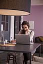 Young woman sitting at table using laptop - CHAF000344