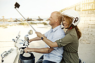 Spain, Majorca, Alcudia, couple with selfie stick on motor scooter - GDF000786
