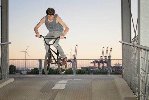 Germany, Hamburg, teenage boy jumping with bmx bike on a parkdeck ramp - MEMF000811