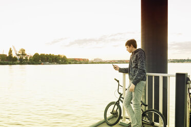 Germany, Hamburg, teenage boy with bmx standing on a jetty using smartphone - MEMF000813
